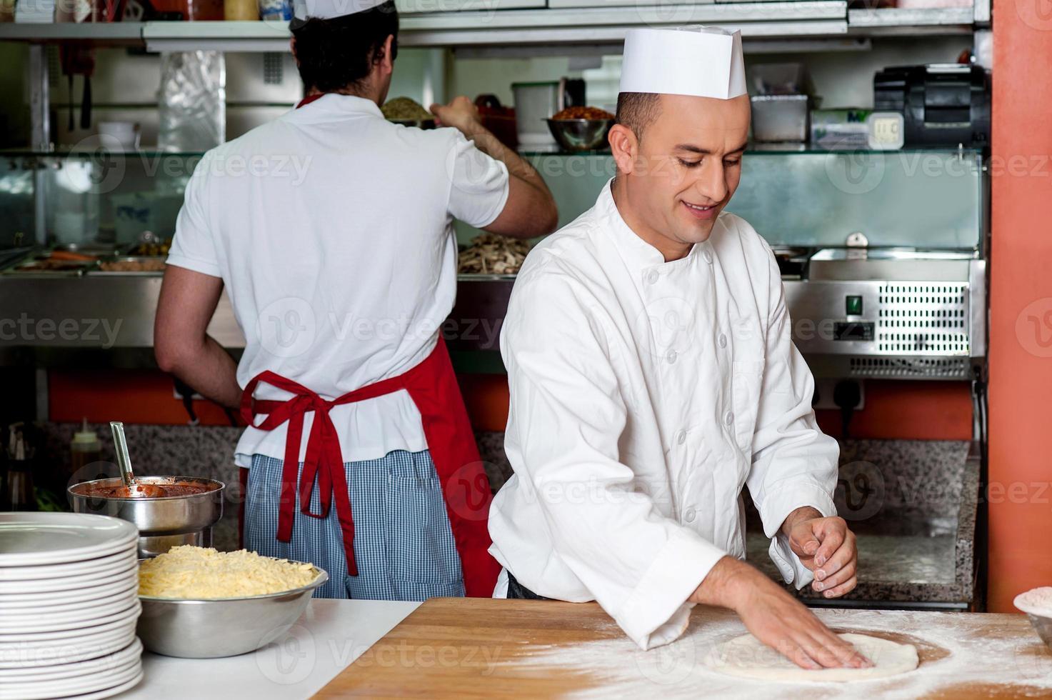 chef che prepara la base per pizza foto