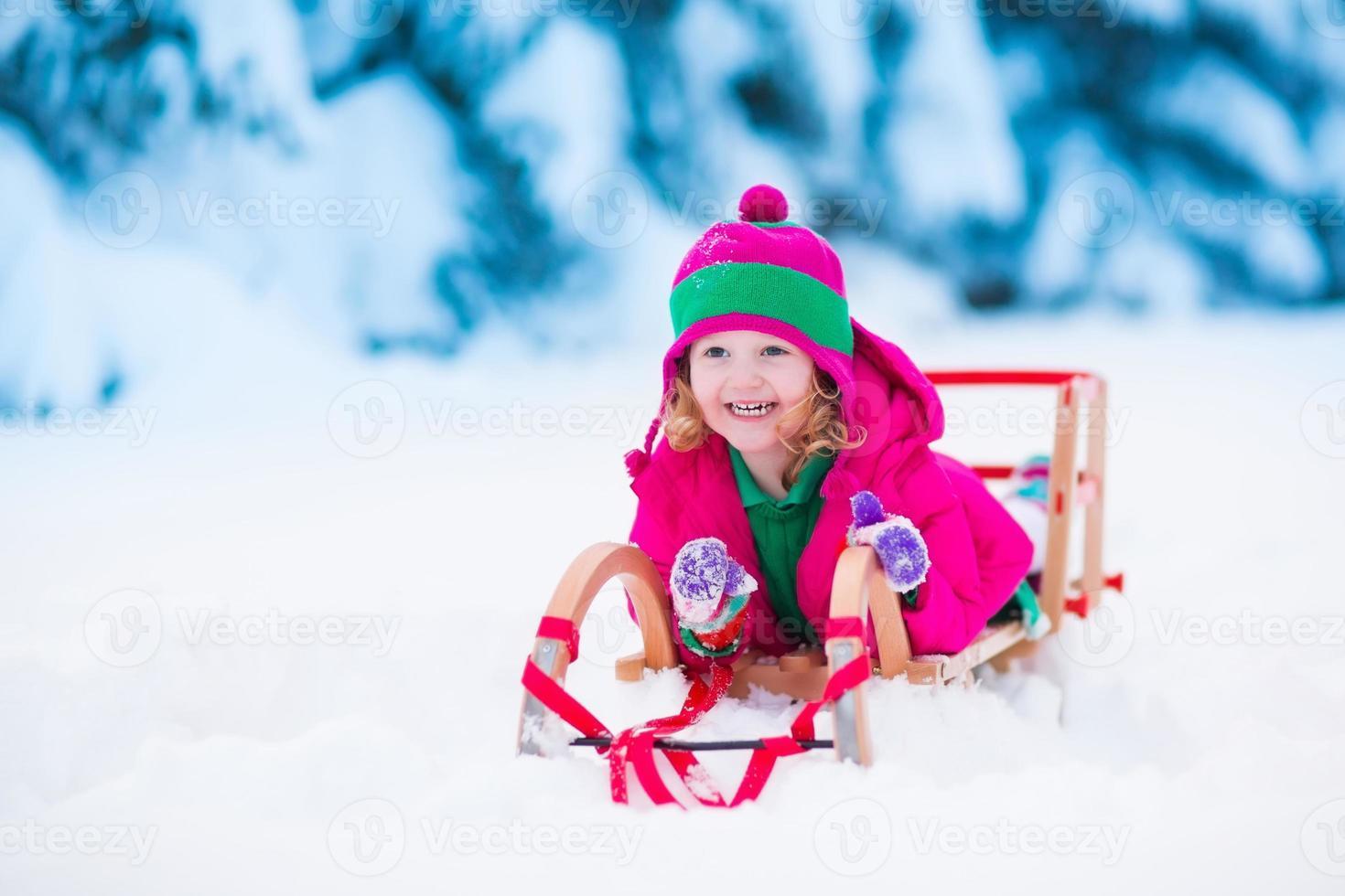 bambina che gioca nella foresta di inverno nevoso foto