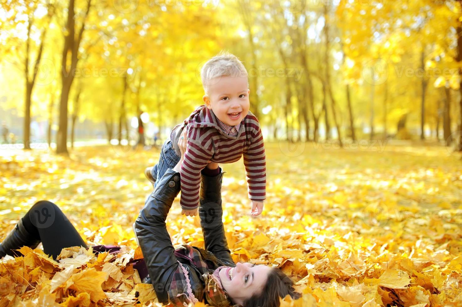 la madre e il bambino a piedi nel parco d'autunno foto
