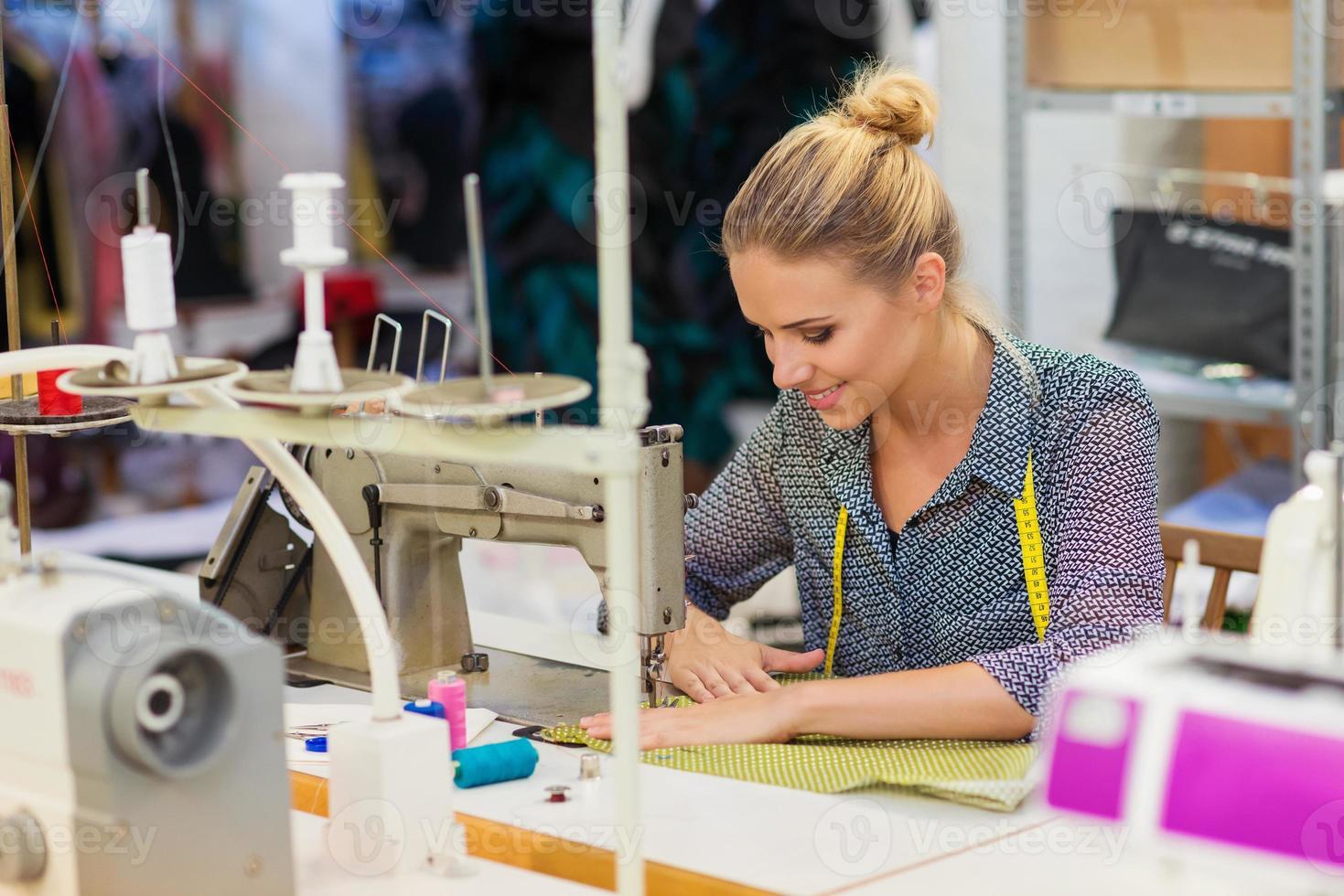 giovane donna con macchina da cucire foto