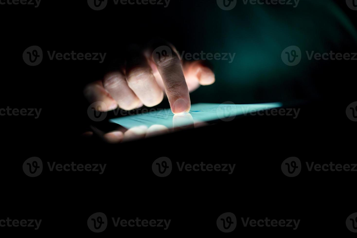 uomo che utilizza un tablet al buio foto