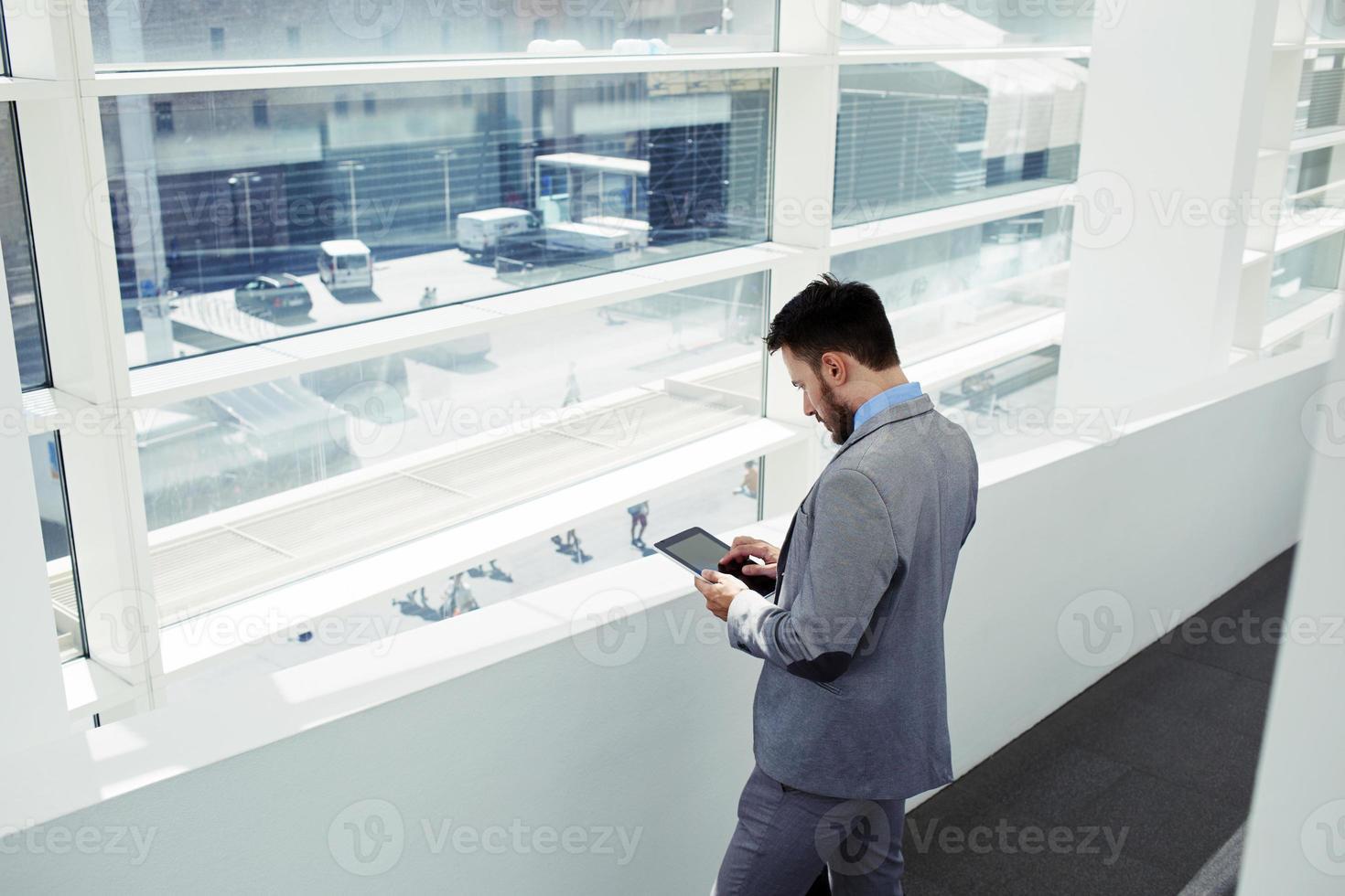 ceo maschio di successo utilizzando la tavoletta digitale durante la pausa di lavoro foto