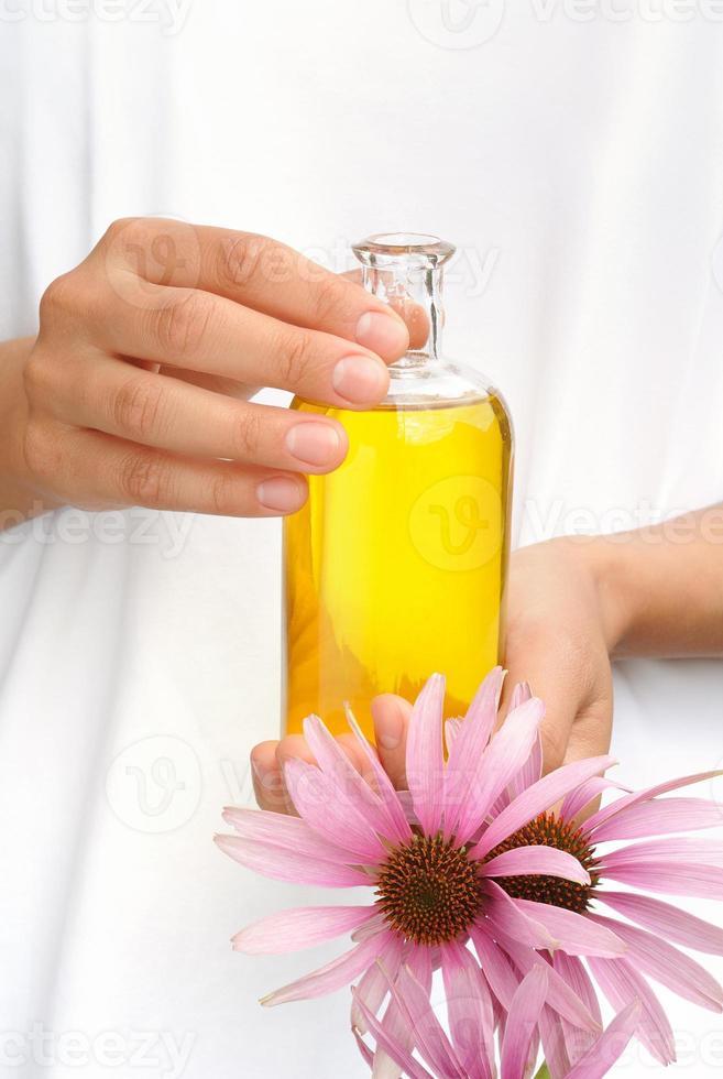 mani che tengono una bottiglia di olio essenziale e coneflowers foto