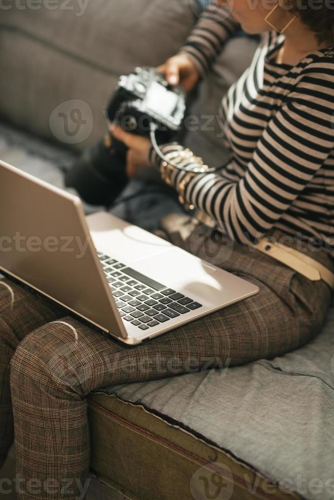 primo piano sulla donna con il computer portatile usando la macchina fotografica moderna della foto del dslr