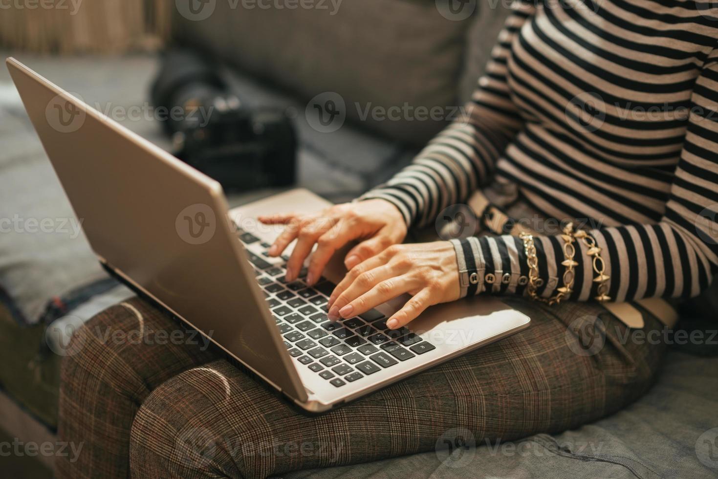 primo piano sulla giovane donna con la macchina fotografica della foto del dslr che per mezzo del computer portatile