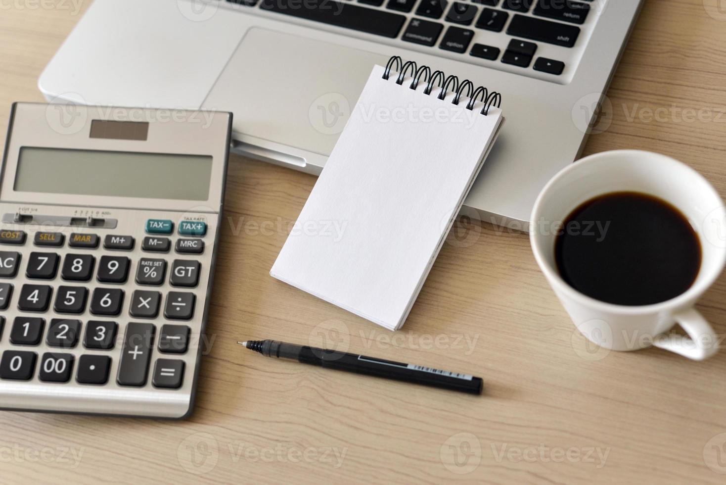 blocco note vuoto, calcolatrice, computer, penna sul tavolo foto