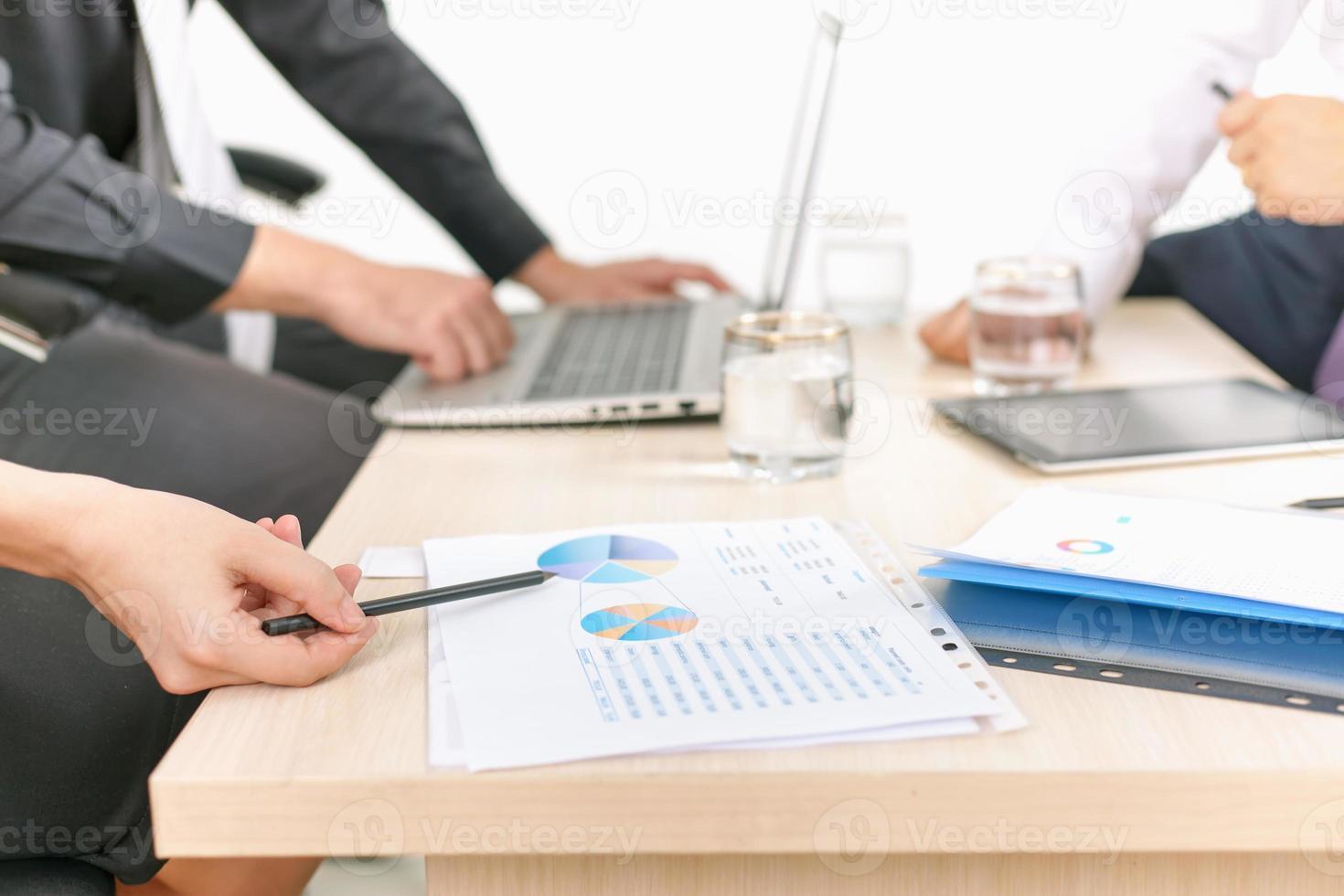 grafico del primo piano e grafici sulla tavola durante la riunione d'affari foto