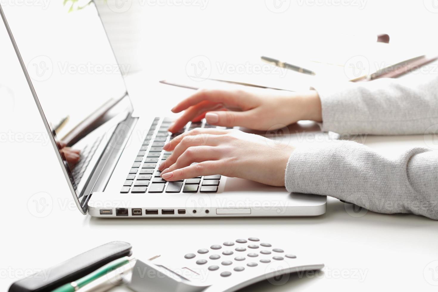 donna di affari che lavora al computer portatile e che calcola i dati foto