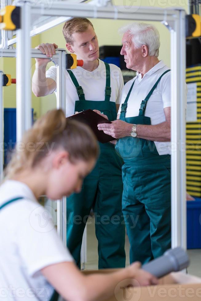 impiegati che lavorano nel capannone di produzione foto