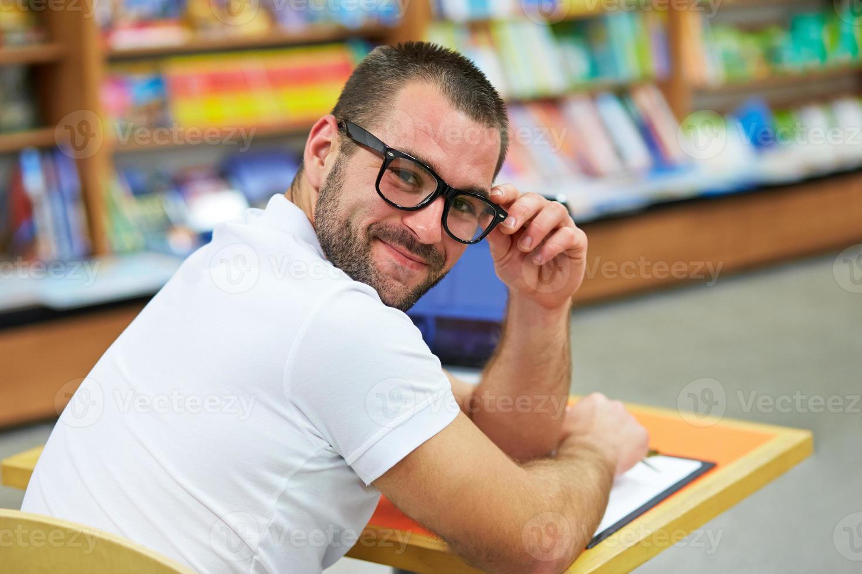 Ritratto di un uomo con gli occhiali in libreria foto