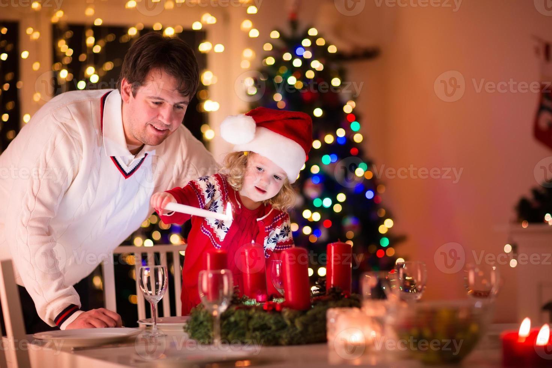padre e figlia che accendono le candele di natale foto
