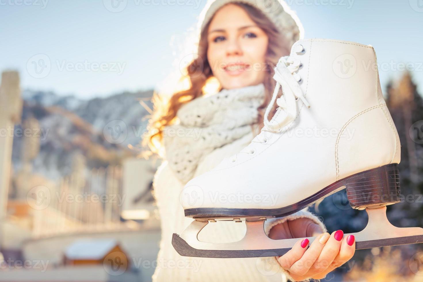 donna caucasica felice che va al pattinaggio su ghiaccio all'aperto foto