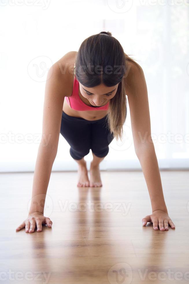 bella giovane donna in buona salute che fa esercizio a casa. foto
