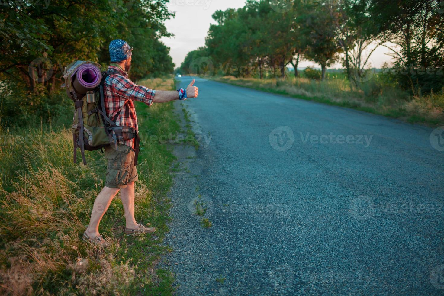 giovane turista caucasico autostop lungo una strada foto