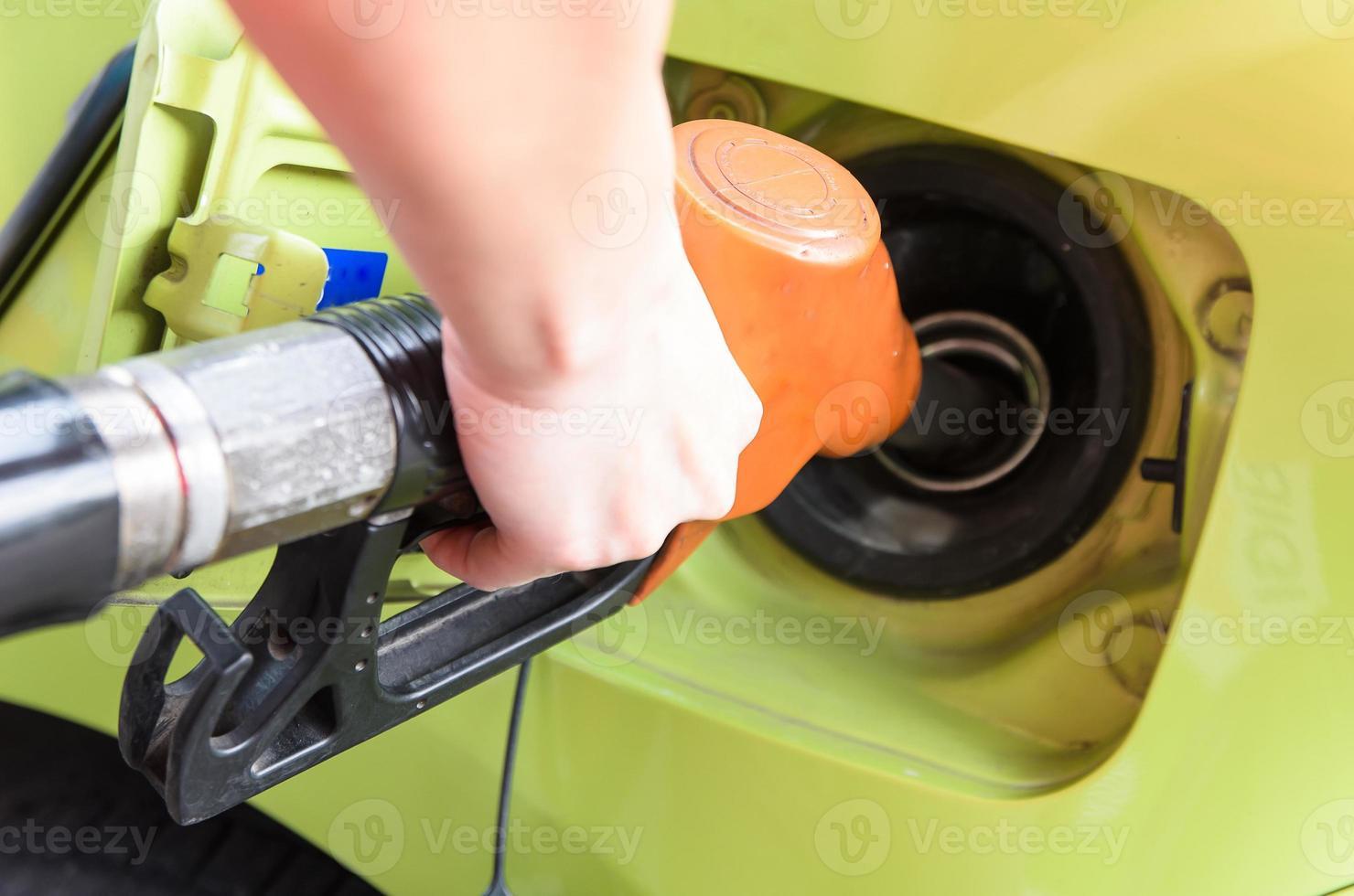 le donne tengono l'ugello del carburante all'auto alla stazione di servizio foto
