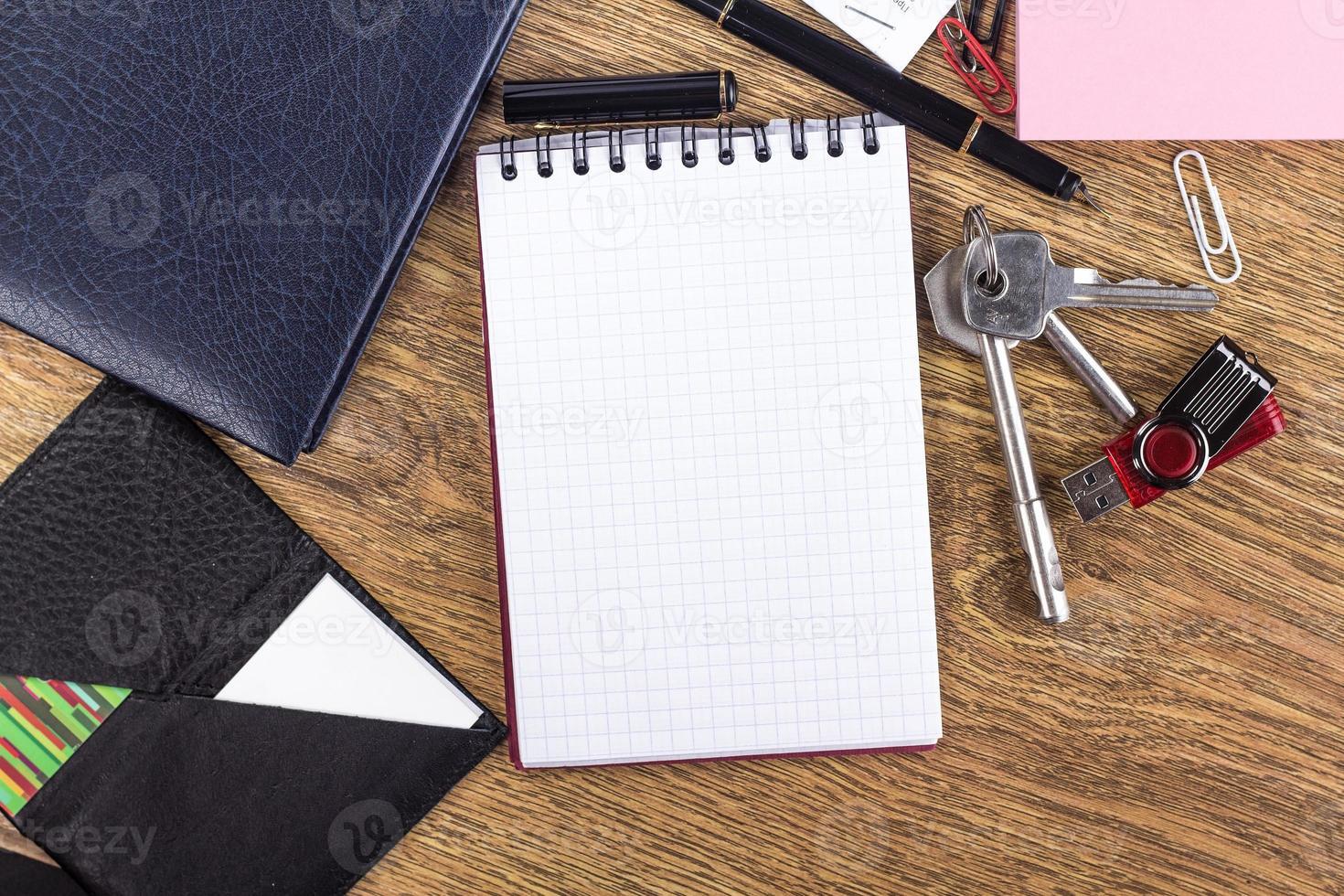 taccuino aperto sulla pagina vuota su sfondo del desktop in legno foto