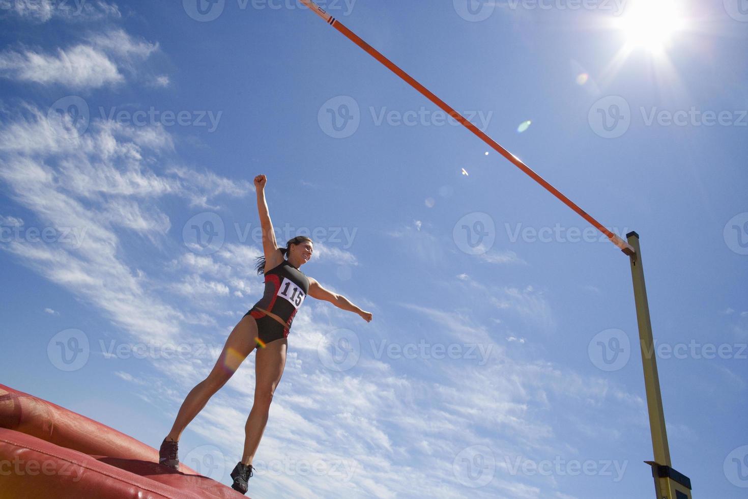 giovane atleta femminile in procinto di saltare oltre la barra (riflesso lente) foto