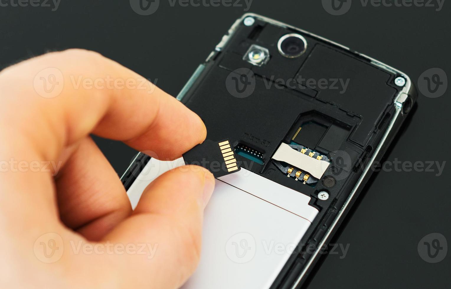 mano maschio che inserisce la micro scheda SD al telefono cellulare. foto
