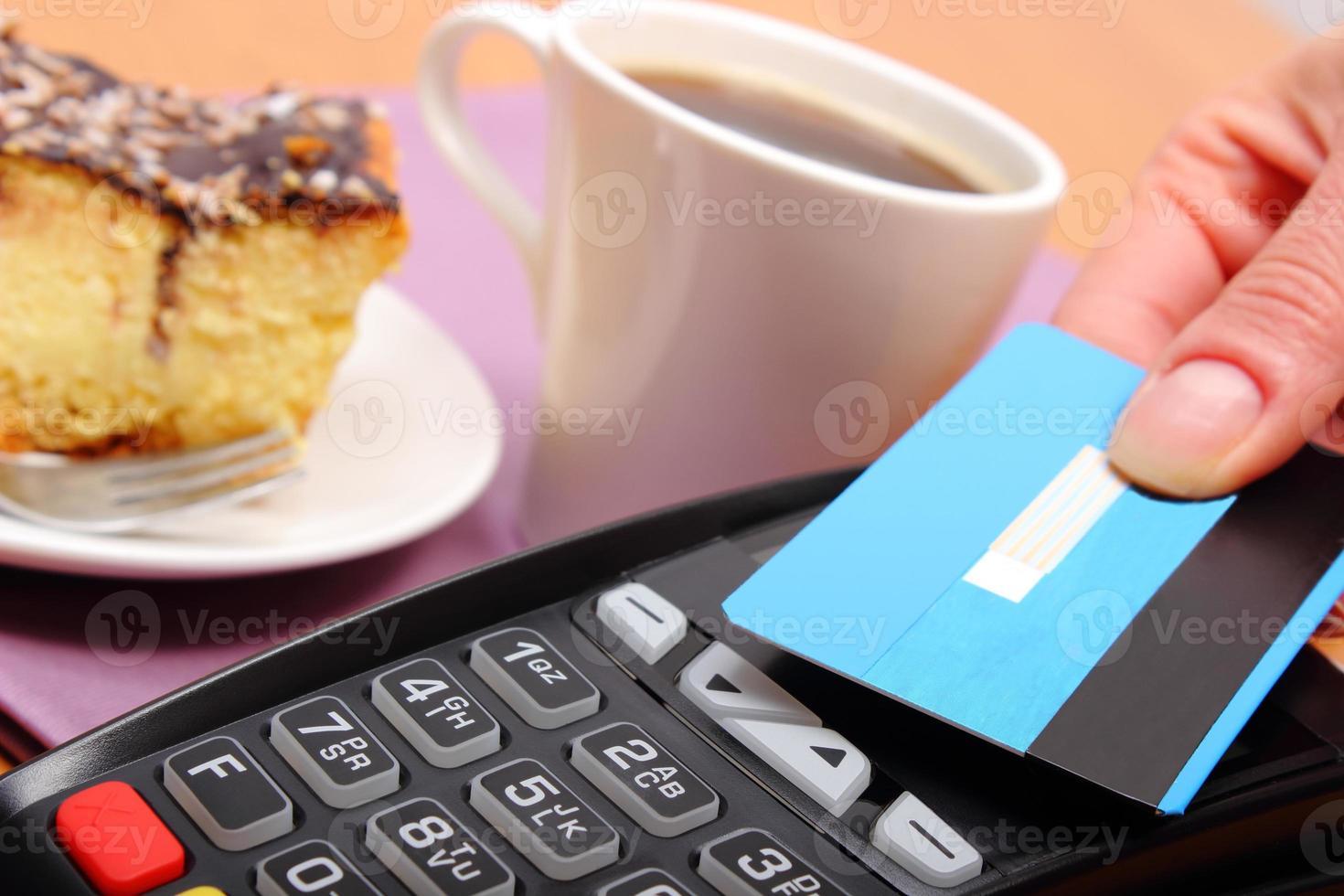pagando con carta di credito senza contatto nella caffetteria, concetto di finanza foto