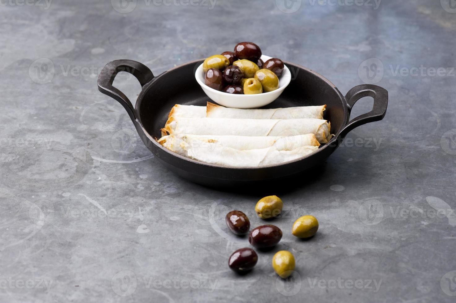 piatto di involtini di formaggio con olive servito in una padella nera foto