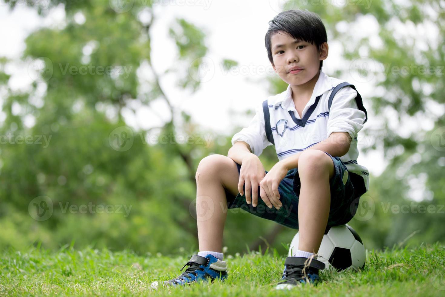 ragazzino asiatico con calcio al parco foto