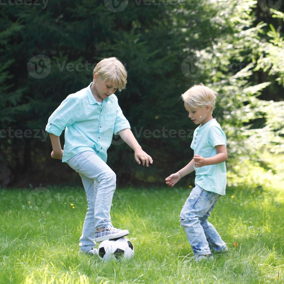 due bambini che giocano a calcio foto
