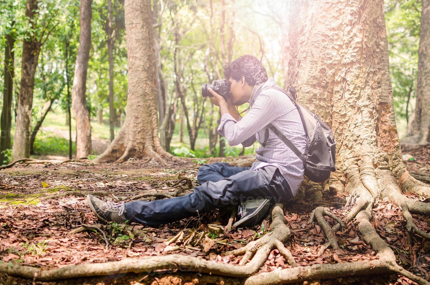 fotografo che scatta foto seduto sotto un grande albero