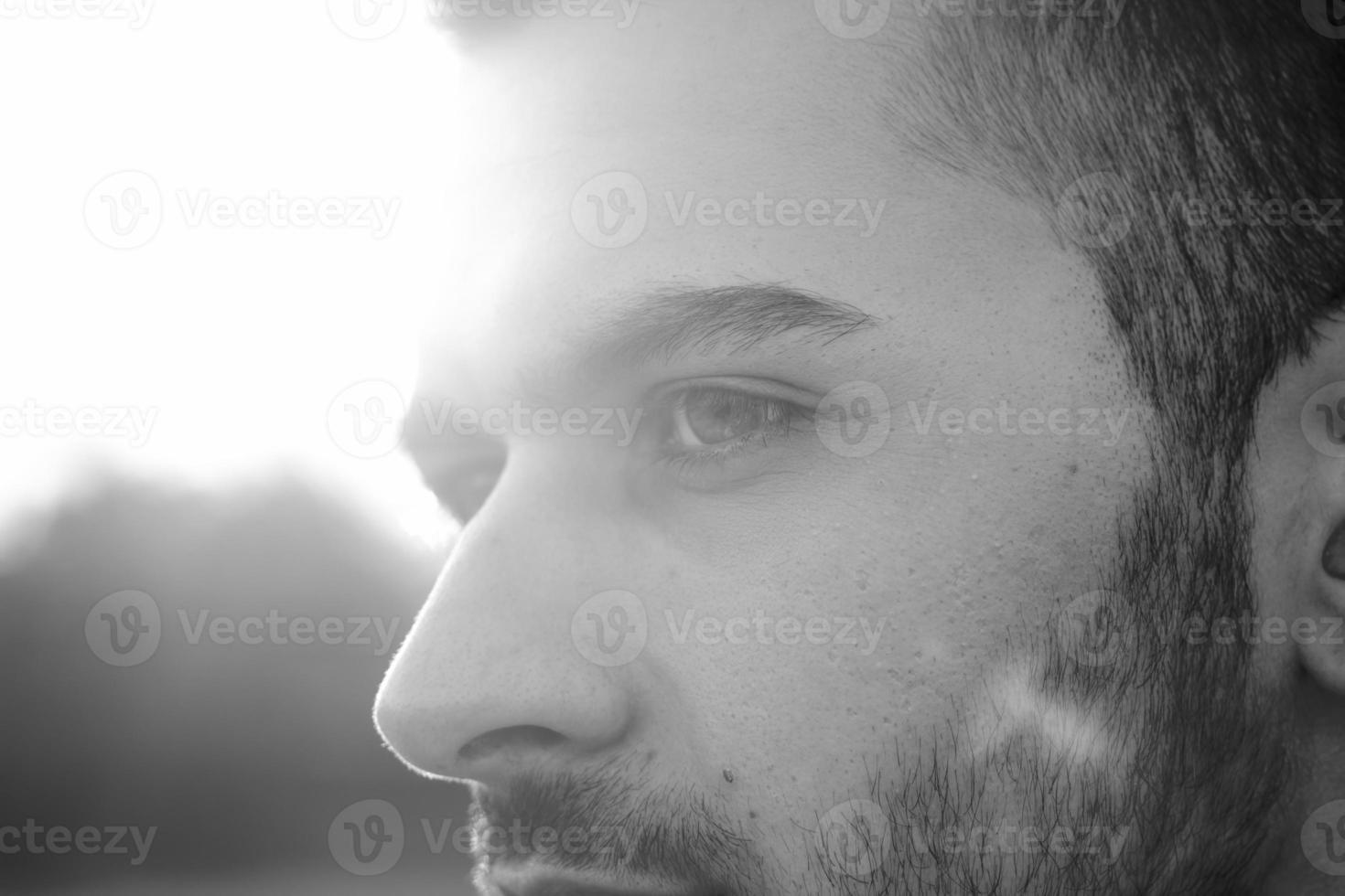 faccia ravvicinata di giovani uomini, forte luce del sole foto