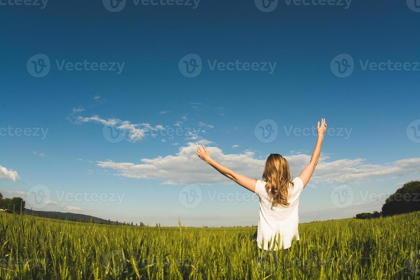 giovane donna che gode della natura e della luce solare nel campo di frumento foto