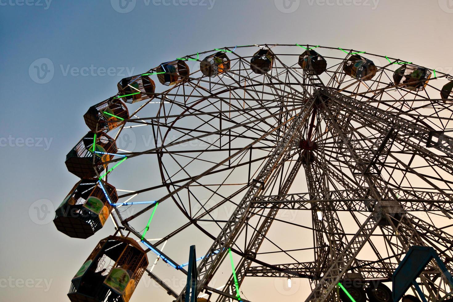 la gente gode della grande ruota nel parco divertimenti foto