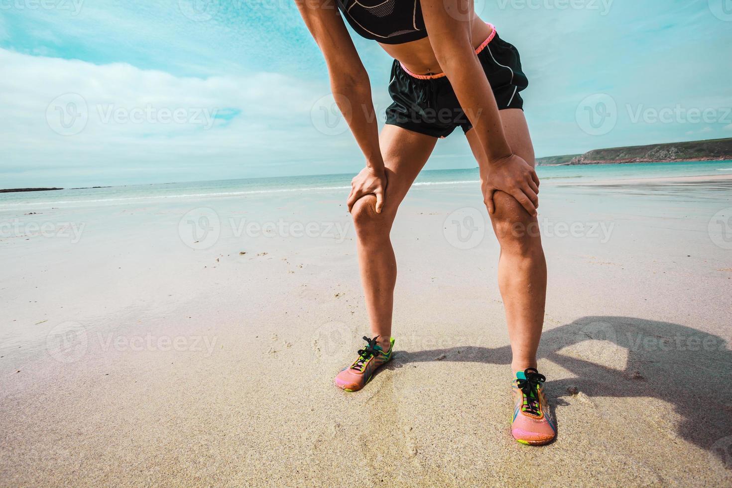 giovane donna atletica che riposa dopo avere corso sulla spiaggia foto