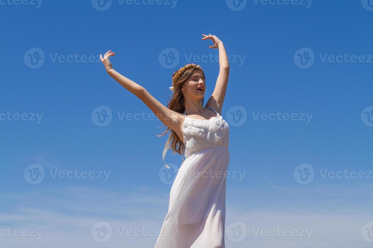 giovane bruna in abito bianco fragile gode il sole estivo foto
