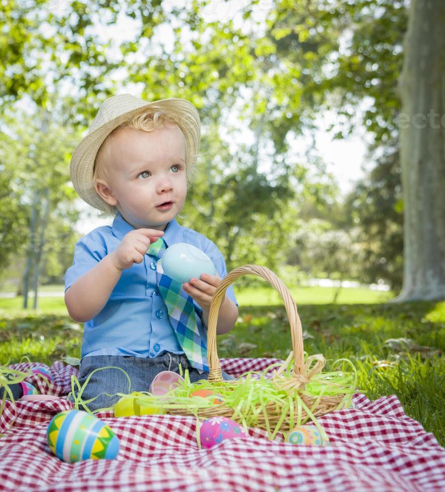 ragazzino sveglio che gode delle sue uova di Pasqua fuori nel parco foto