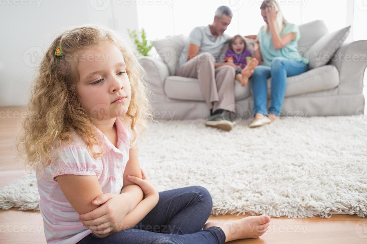 ragazza arrabbiata che si siede sul pavimento mentre i genitori godono con il fratello foto