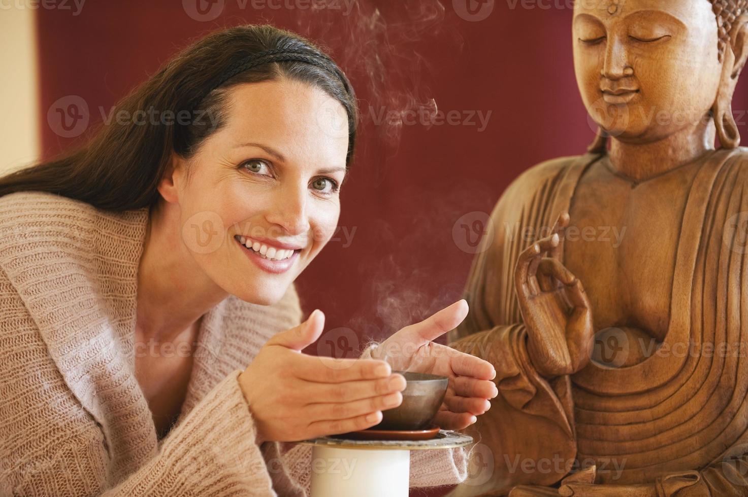 donna castana che gode della statua di Buddha del profumo del bastoncino d'incenso nel fondo foto