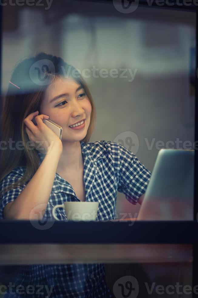 asia donna felice parla al telefono nella caffetteria e godersi il caffè foto