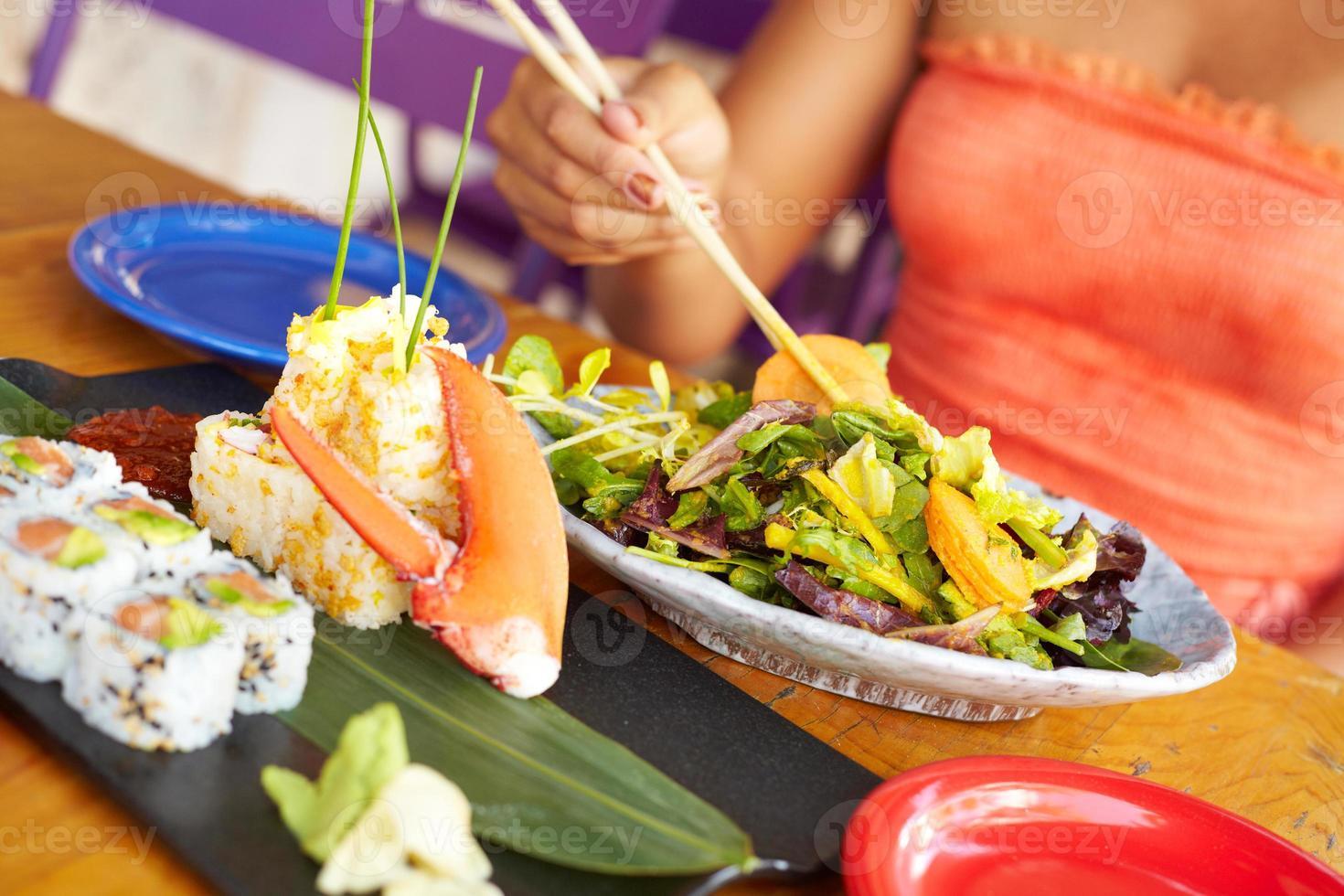 Colse in su della donna di razza mista godendo il pasto al ristorante foto