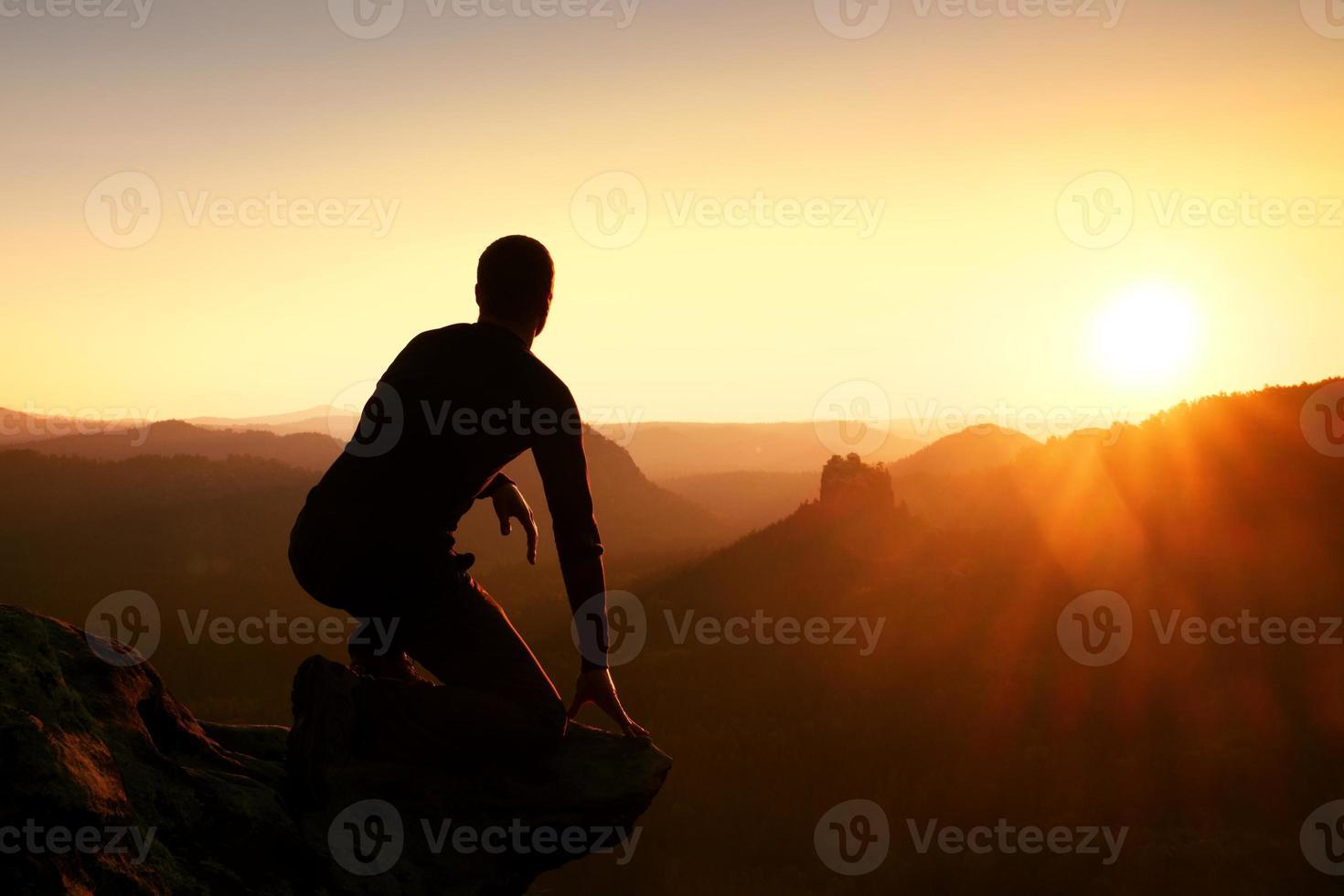 l'escursionista si rilassa e si gode il tramonto all'orizzonte. effetto vivido. foto