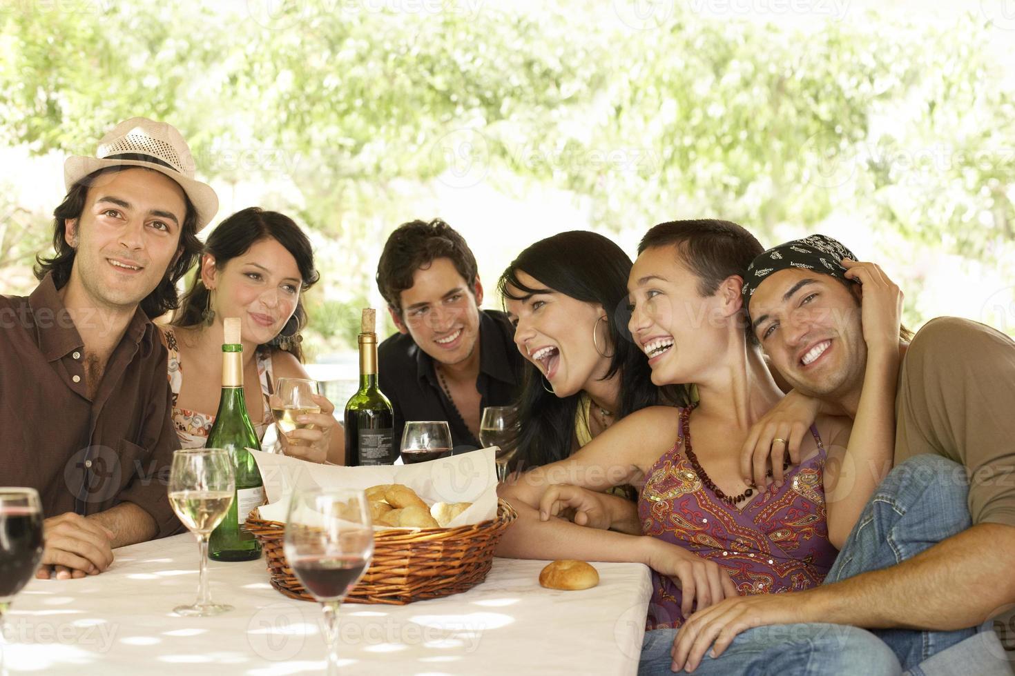 amici con bevande e cestino del pane a tavola godendo la festa foto
