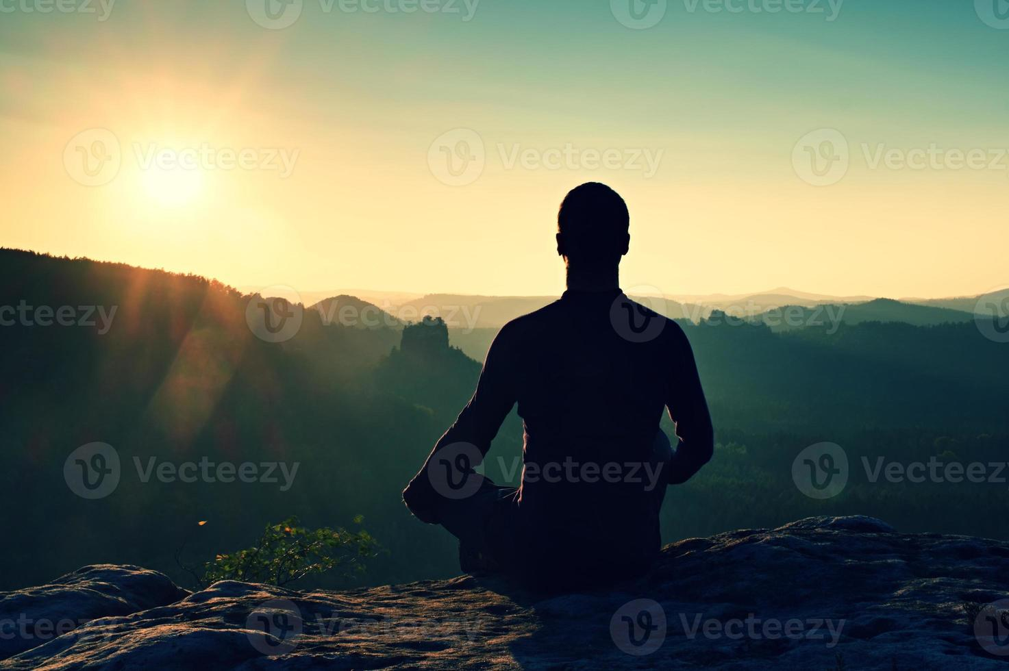 escursionista in posizione accovacciata su una roccia, goditi il panorama del crepuscolo foto