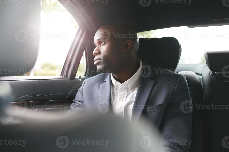 uomo d'affari africano in viaggio per lavorare in auto di lusso foto