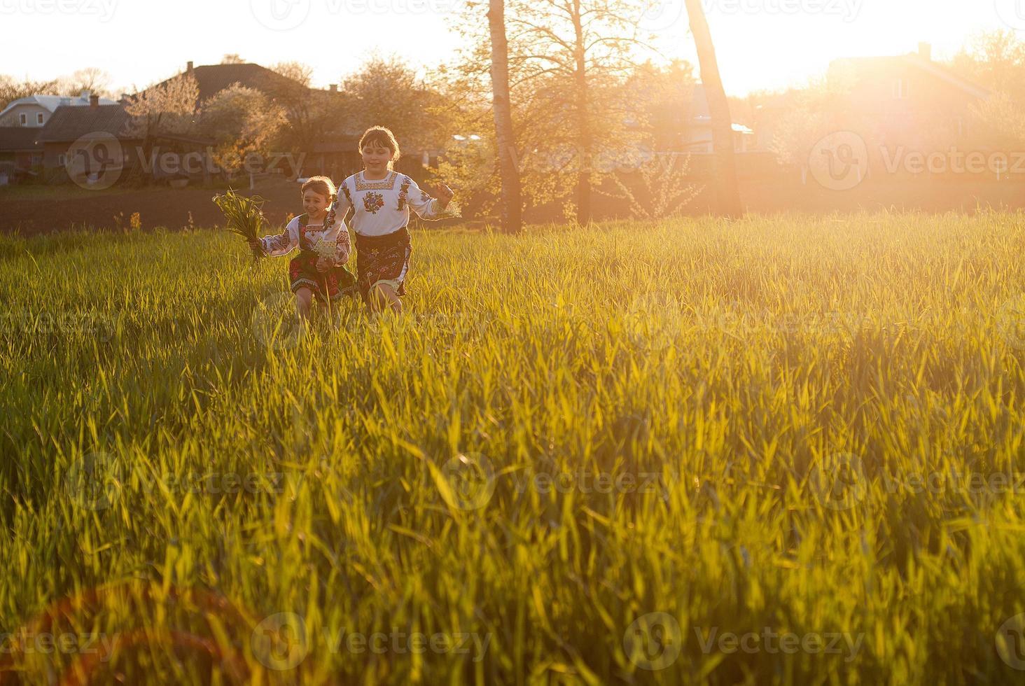 due bambine che corrono nel campo di erba alta foto