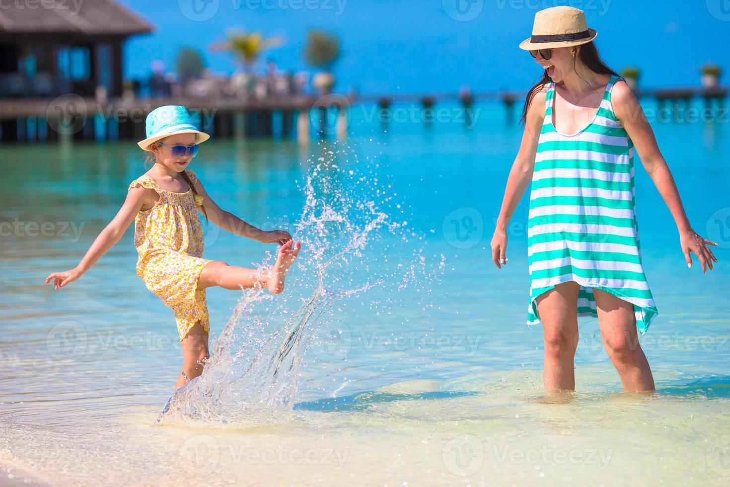 madre e figlia godendo il tempo in spiaggia tropicale foto