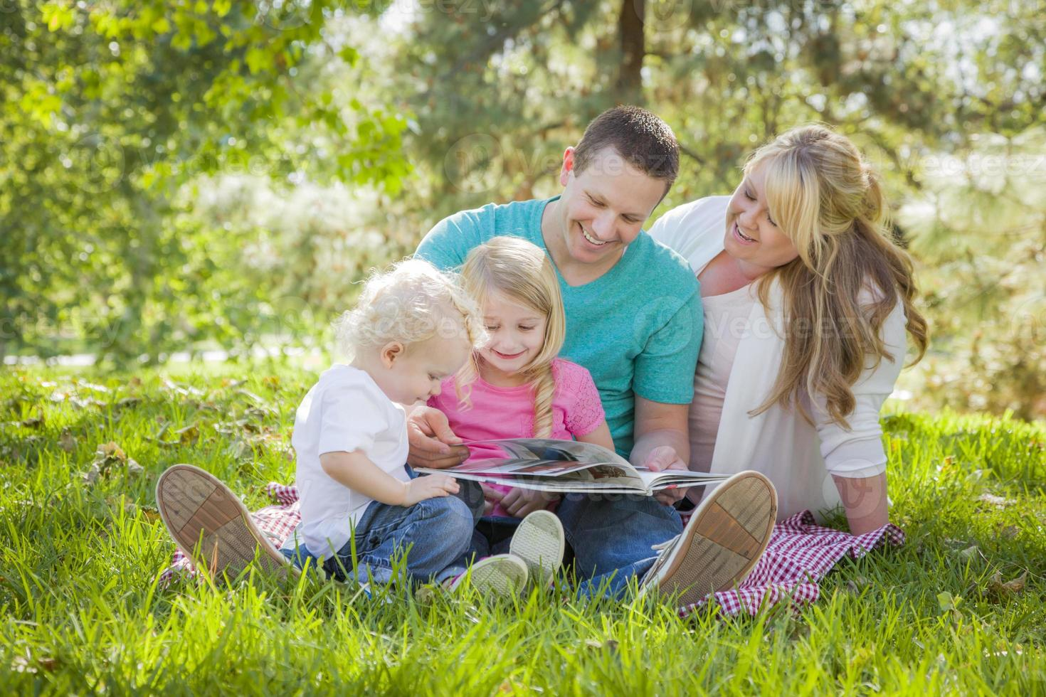 la giovane famiglia ama leggere un libro nel parco foto