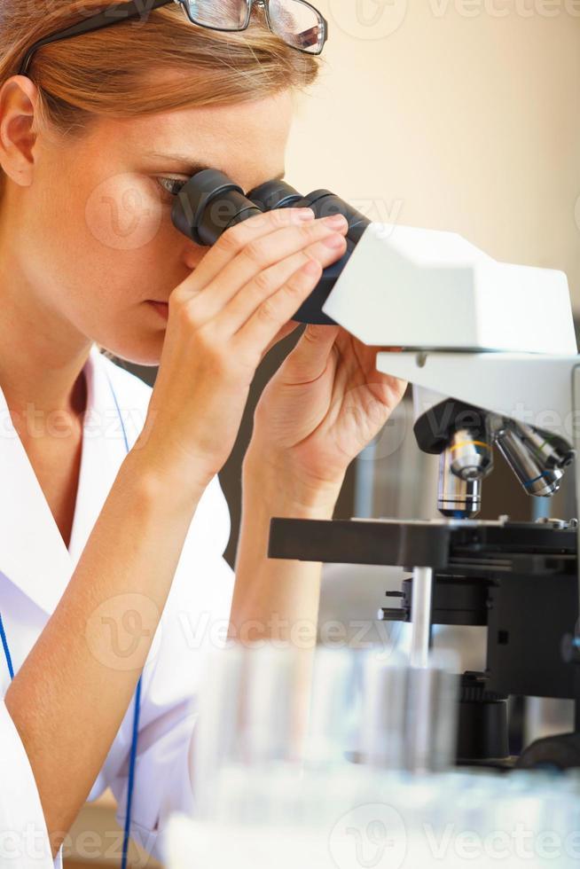 donna che lavora con un microscopio. foto