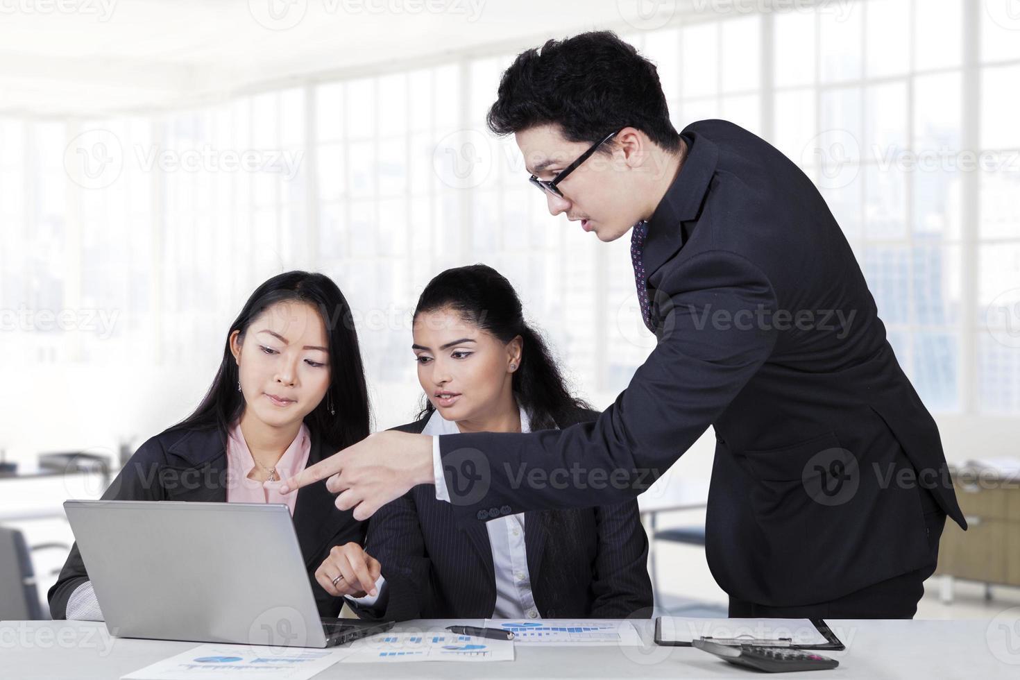manager che punta al computer portatile in riunione foto