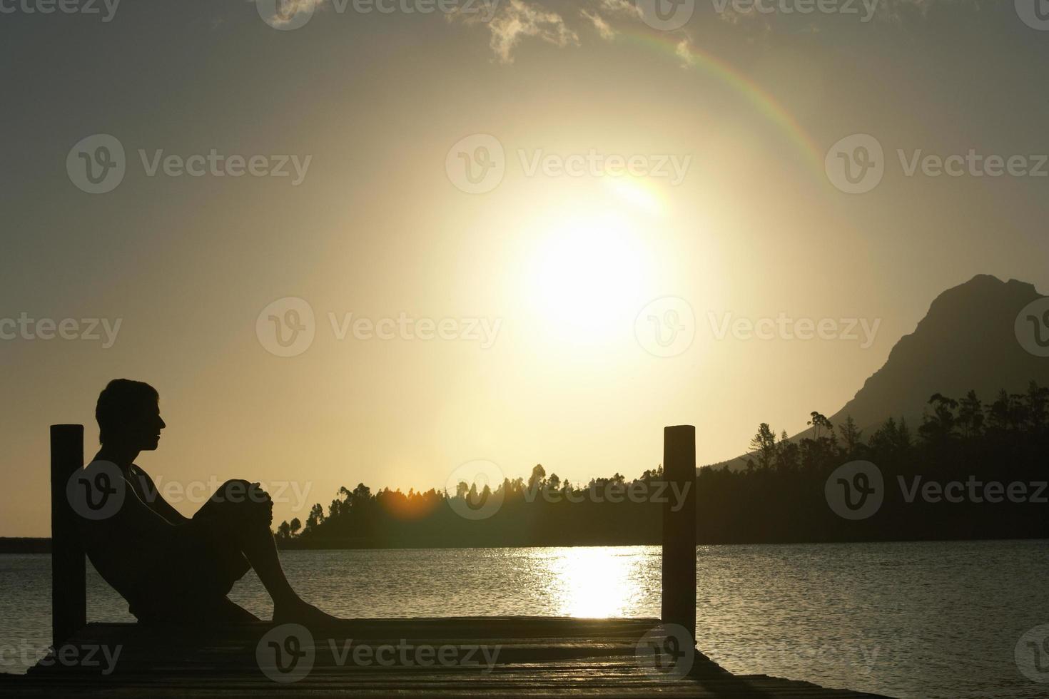 uomo seduto sul molo sul lago foto