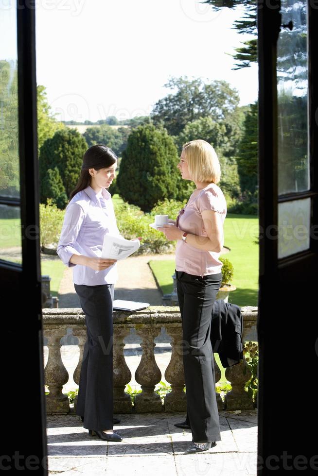 imprenditrice in conversazione con il collega all'aperto, vista thro foto