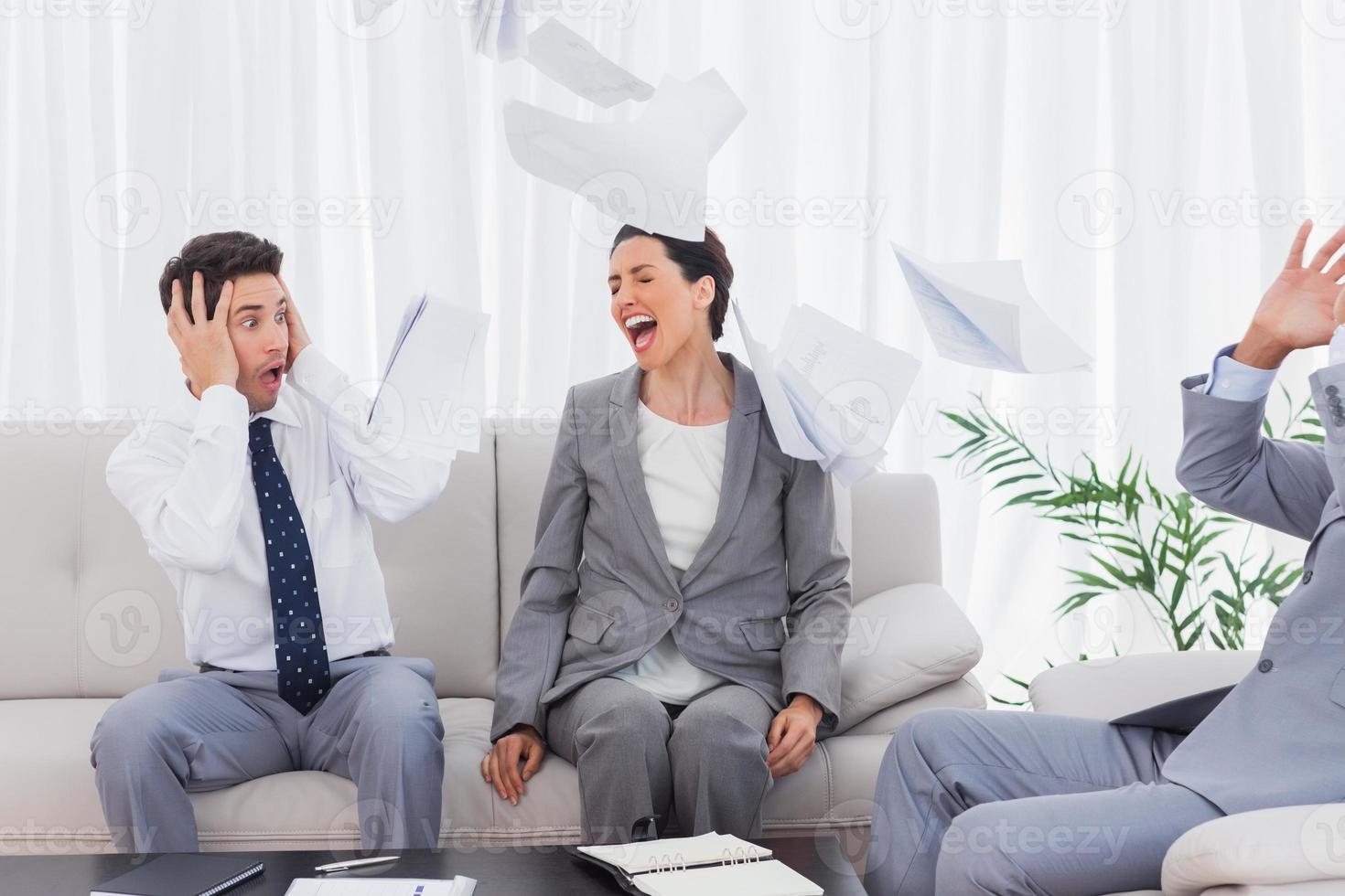 uomini d'affari scioccati dal collega che urla e lancia documenti foto