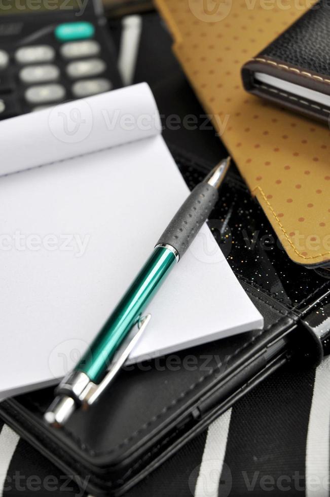 penna messa su blocco note vuoto foto